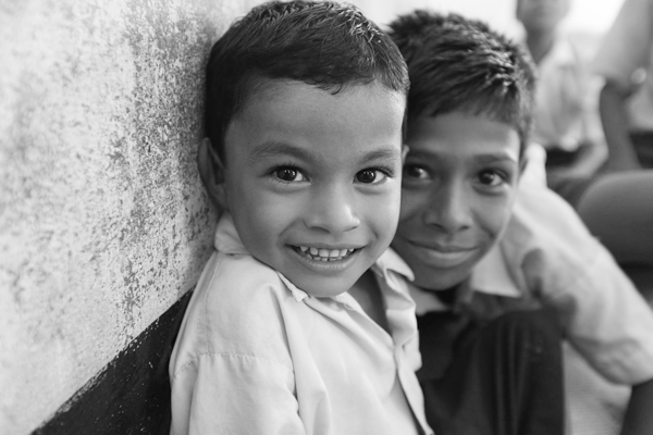two immigrant boys smiling by a wall